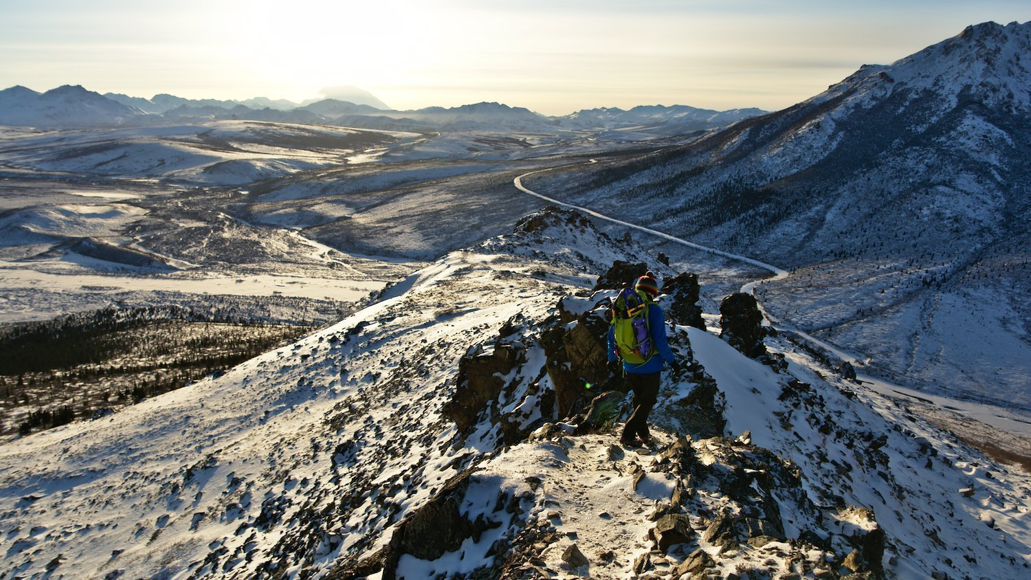 Hiker descending the Savage Alpine Trail to the Savage River in Denali National Park in winter.