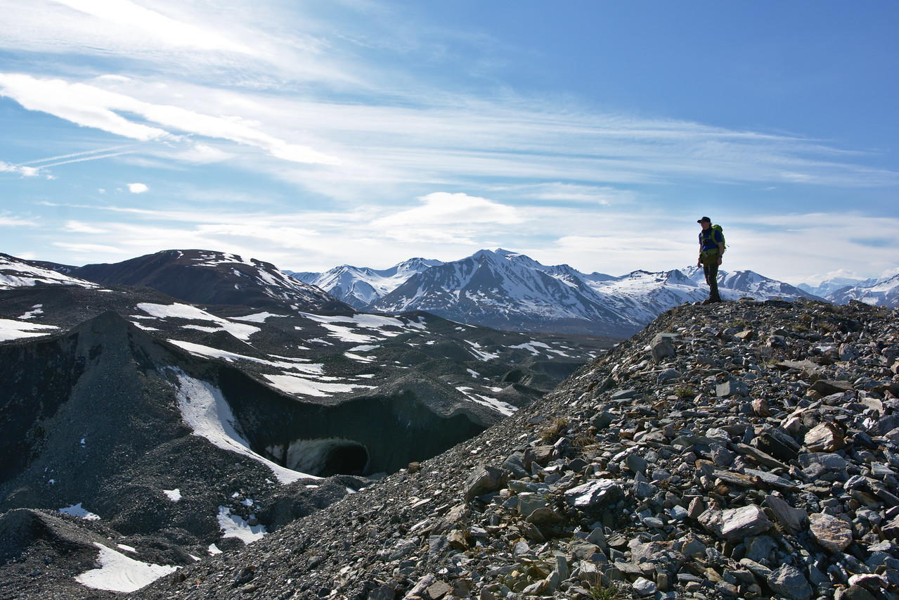 A hiker overlooking an ice cave on the Canwell Glacier.